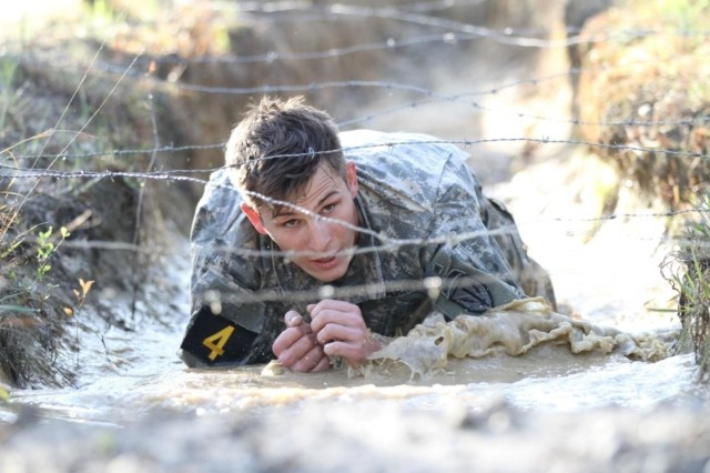 Staff Sgt. William Haney crawls through a mud obstacle, part of the 2014 Best Ranger Competition.
