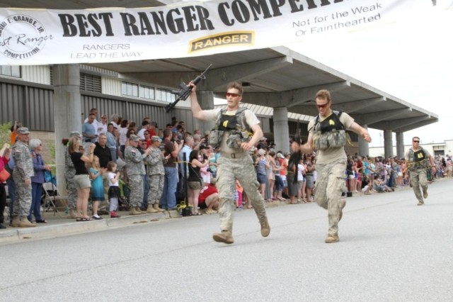"""Staff Sgt. William Haney and Sgt. Brendon Wellendorf cross the finish line of the final """"buddy run"""" segment of the 2014 Best Ranger competition."""