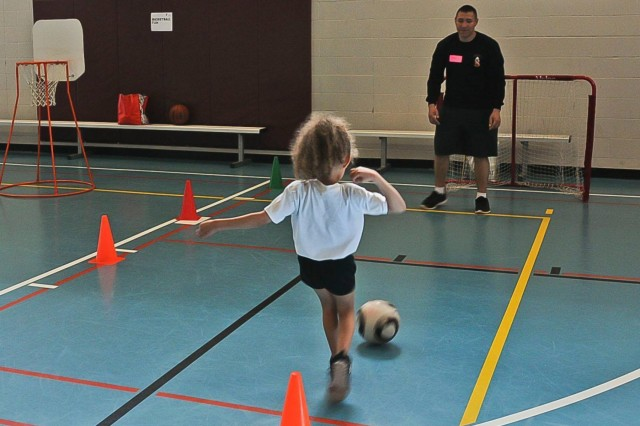 A Soldier with the 2nd Battalion, 17th Field Artillery, 2-2 Stryker Brigade Combat Team, 7th Infantry Division plays soccer with a kid at the Lakewood, Wash. Young Men Christian Association during a Healthy Kids Day event, April 26. Healthy Kids Day is a national initiative and every YMCA in the US is encouraged to participate.