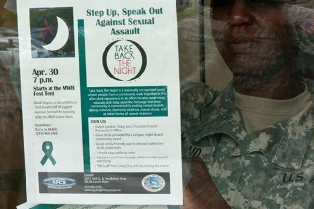 Sgt. 1st class Latissa Edmond, a Jackson, Ala. native and sexual assault response coordinator for the 2-2 Stryker Brigade Combat Team, 7th Infantry Division, hangs sexual assault awareness posters around the 2-2 SBCT headquarters, April 17. April is the 10th annual Sexual Assault Awareness Month.