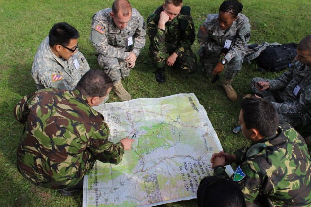 Romanian soldiers and U.S. Army ROTC cadets study a terrain map in preparation for land navigation training during the Cadets 2013 CULP mission to Romania. Their purpose was to teach conversational English to Romanian troops, train with the troops and learn something about the local language and culture. The host countries ask for this training because of English speaking NATO requirements, which bring stability to their regions.