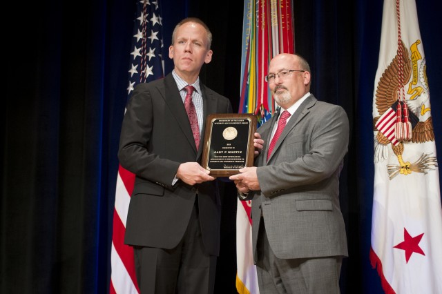 Under Secretary of the Army Brad R. Carson presents Gary P. Martin with the Diversity and Leadership Programs Award, Diversity and Leadership Award, during the 2014 Secretary of the Army Awards ceremony, at the Pentagon, May 5, 2014.