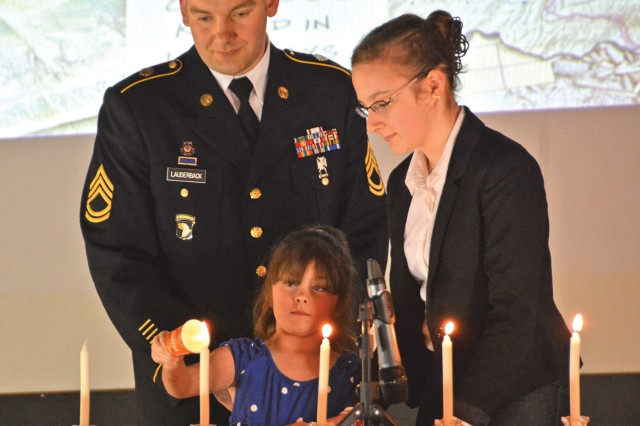 Sgt. 1st Class Edwin Lauderback, U.S. Army Garrision Wiesbaden's Equal Opportunity adviser, looks on as members of Wiesbaden's Jewish community ligh candles during the community's Holocaust Remembrance Day commemoration on Clay Kaserne April 29.