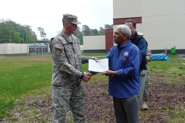 Staff Sgt. Michael Ramage (left), a U.S. Army Europe Soldier and volunteer at the Ramstein Air Base's passenger terminal's United Service Organization is presented a Certificate of Achievement by Clarence Jeffries, manager of the Ramstein PAX USO, May 1, for his quick reaction and first-responder skills, which ultimately saved a man's life.