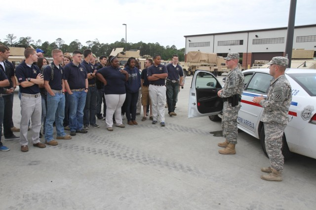 Spc. Lawrence Boroff, right, and Spc. Robert Cross, second from right, both military police soldiers with Headquarters and Headquarters Company 4-3 Brigade Special Troops Battalion, 4th Infantry Brigade Combat Team, 3rd Infantry Division, speak to cadets from Southeast Bulloch County High School's Junior Reserve Officers Training Corps program about the daily duties of military police, May 2, 2014, on Fort Stewart, Ga.  (U.S. Army Photo by Sgt. Bob Yarbrough, 4th IBCT, 3rd ID, Public Affairs)