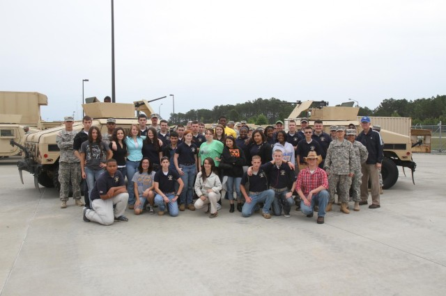 Soldiers with Headquarters and Headquarters Company, 4-3 Brigade Special Troops Battalion, 4th Infantry Brigade Combat Team, 3rd Infantry Division, and cadets from Southeast Bulloch County High School's Junior Reserve Officers Training Corps pose for a photo after hands-on demonstrations of vehicles and equipment at the 4-3 BSTB motor pool, May 2, 2014, on Fort Stewart, Ga. (U.S. Army Photo by Sgt. Bob Yarbrough, 4th IBCT, 3rd ID, Public Affairs)