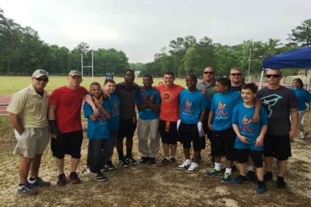 Soldiers from Company C, 3rd Battalion, 15th Infantry Regiment, 4th Infantry Brigade Combat Team, 3rd Infantry Division, stand with young competitors of the Liberty County Special Olympics, April 25, 2014, at the Liberty County Recreation Center in Hinesville, Ga. The soldiers were paired with the competitors and cheered the competitors during a series of events. (U.S. Army Photo by 2nd Lt. Jared Gray, 3-15 Inf., 4th IBCT, 3rd ID, UPAR)