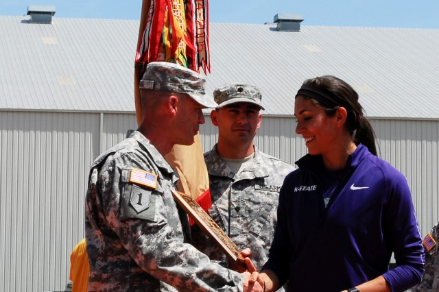 "Lt. Col. C.J. King, commander of 299th BSB, 2nd ABCT, 1st Inf. Div., presents the ""Heartbeat of the Team"" award to Sarah Kolmer, a junior combined events specialist with the KSU Track & Field Team, May 3 during the Ward Haylett Invitational track meet at R.V. Christian track complex in Manhattan, Kan. The award was given to the student-athlete who has excelled in the classroom and on the track, as well as demonstrated high moral character in keeping with the Army values."
