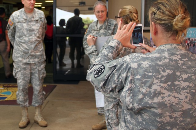 A spectator captures a staff member displaying nursing week material to Brig. Gen. Dennis Doyle (left), Commanding General of Pacific Regional Medical Command and Tripler Army Medical Center during the National Nurses Week kick off ceremony on May 6, 2014. National Nurses Week is an annual celebration where nurses from all fields are recognized for their outstanding contributions to medicine.
