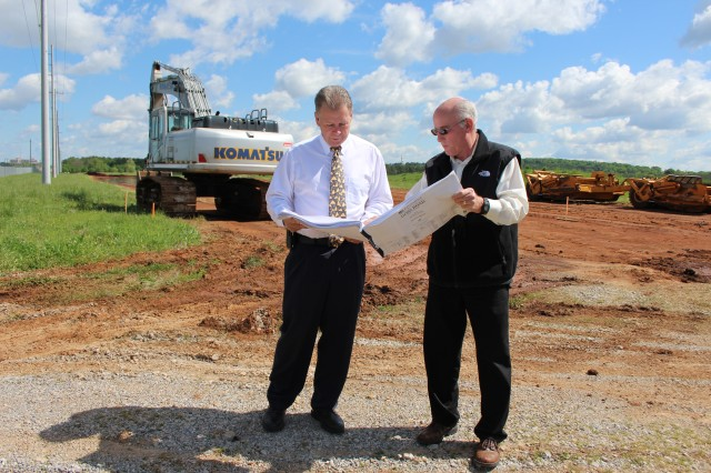 Joe Davis, left, and Lee Riddle look over plans for the construction of the Goss Road realignment. Top soil stripping shown behind them is being done in preparation for the realignment. The project will be completed by the end of 2014.