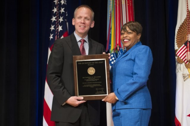 Photo Credit: Staff Sgt. Bernardo Fuller Under Secretary of the Army Brad R. Carson presents Nancy Small with the Small Business Utilization Award for Maj. Gen