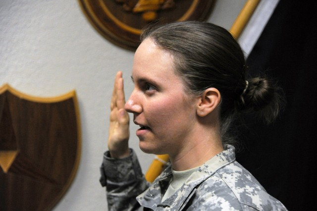 Sgt. Meredith Schwartzentruber, a III Corps G3 Operations Section Soldier, says an oath of enlistment to the Texas National Guard as the first Soldier to sign a contract under the new AC2RC program, May 1, 2014 at the Copeland Center, at Fort Hood, Texas.