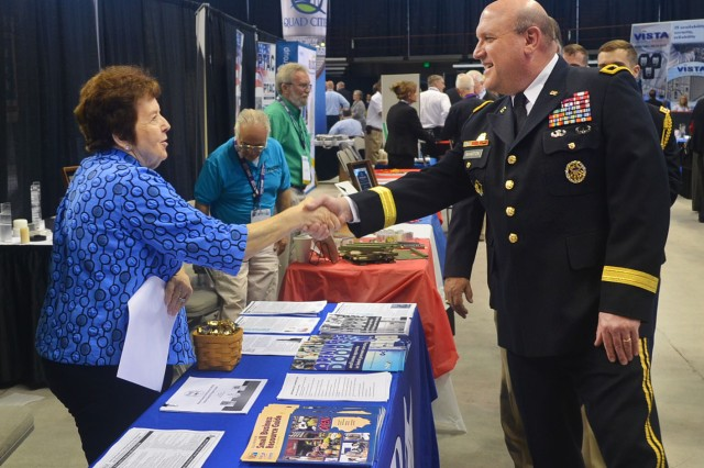 Maj. Gen. John F. Wharton, commanding general of U.S. Army Sustainment Command and Rock Island Arsenal, greets Barbara A. Merz, U.S. Small Business Administration (Cedar Rapids, Iowa branch office), at the 2014 Midwest Small Business Government Contracting Symposium at the I-wireless Center in Moline, Ill., May 7. Hundreds of small business leaders from around the nation gathered at the annual event to learn about business opportunities with the U.S. Army. Headquartered at Rock Island Arsenal, Ill., the home of Army Logistics, ASC supports combatant commands around the globe.