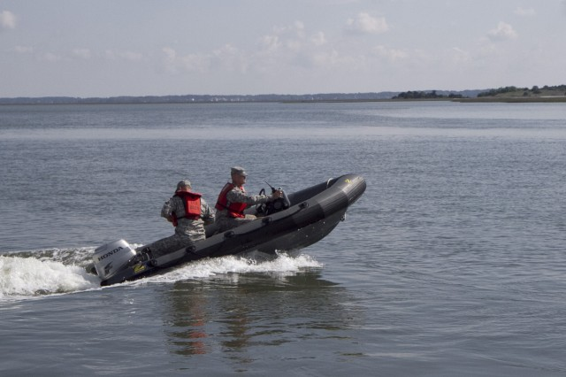 Soldiers of the 824th Transportation Company (Heavy Watercraft) quickly responded to an explosion of a 28-foot fishing boat that occurred at the civilian side of the North Carolina State Port in Morehead City on April 3. They assisted in first aid and damage control until civilian authorities arrived. Here, Chief Warrant Officer Randy Grady, left, and Warrant Officer Candidate Robert Wallace race to the scene with fire extinguishers.