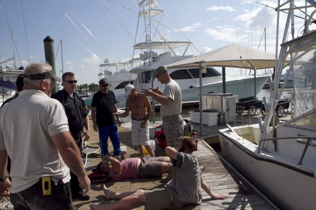 Soldiers of the 824th Transportation Company (Heavy Watercraft) quickly responded to an explosion of a 28-foot fishing boat that occurred at the civilian side of the North Carolina State Port in Morehead City on April 3. They assisted in first aid and damage control until civilian authorities arrived. Here, Chief Warrant Officer Randy Grady tries to explain to one of the victims what he believes may have happened.