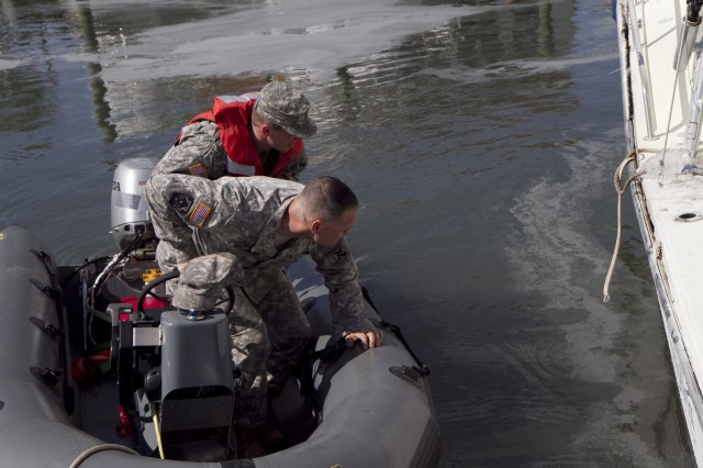 Soldiers of the 824th Transportation Company (Heavy Watercraft) quickly responded to an explosion of a 28-foot fishing boat that occurred at the civilian side of the North Carolina State Port in Morehead City on April 3. They assisted in first aid and damage control until civilian authorities arrived. Pictured here, Staff Sgt. Bryan Hanlon, back, and Warrant Officer Candidate Robert Wallace inspect the damage to the boat to make sure it won't sink.