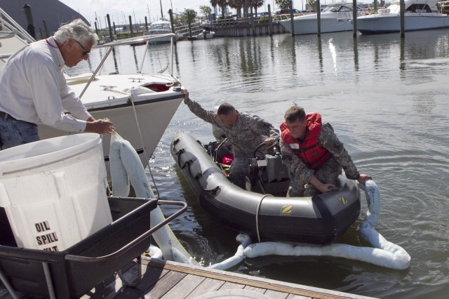 Soldiers of the 824th Transportation Company (Heavy Watercraft) quickly responded to an explosion of a 28-foot fishing boat that occurred at the civilian side of the North Carolina State Port in Morehead City on April 3. They assisted in first aid and damage control until civilian authorities arrived. Pictured here are Warrant Officer Candidate Robert Wallace, driving the rescue boat and Staff Sgt. Bryan Hanlon, handling an absorbent boom.