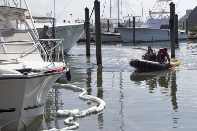 Soldiers of the 824th Transportation Company (Heavy Watercraft) quickly responded to an explosion of a 28-foot fishing boat that occurred at the civilian side of the North Carolina State Port in Morehead City on April 3. They assisted in first aid and damage control until civilian authorities arrived. Here a spillage response boom is secured to prevent further contamination of the water by fuel and other possible hazardous material. Pictured here are Chief Warrant Officer 3 Randy Grady, on the dock, Warrant Officer Candidate Robert Wallace, driving the rescue boat and Staff Sgt. Bryan Hanlon, handling the containment boom.