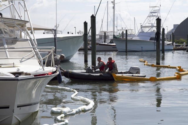 Soldiers of the 824th Transportation Company (Heavy Watercraft) quickly responded to an explosion of a 28-foot fishing boat that occurred at the civilian side of the North Carolina State Port in Morehead City on April 3. They assisted in first aid and damage control until civilian authorities arrived. Here a spillage response boom is secured to prevent further contamination of the water by fuel and other possible hazardous material. Pictured here are Chief Warrant Officer 3 Randy Grady, on the dock, Warrant Officer Candidate Robert Wallace, driving the rescue boat, and Staff Sgt. Bryan Hanlon, handling the containment boom.