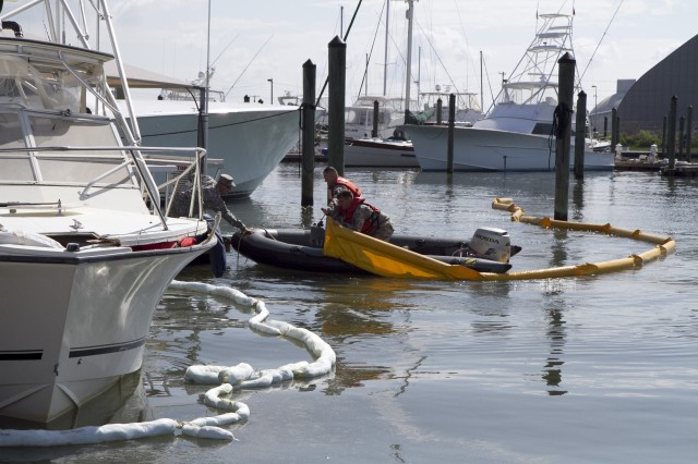 Soldiers of the 824th Transportation Company (Heavy Watercraft) quickly responded to an explosion of a 28-foot fishing boat that occurred at the civilian side of the North Carolina State Port in Morehead City on April 3. They assisted in first aid and damage control until civilian authorities arrived. Here a spillage response boom is emplaced to prevent further contamination of the water by fuel and other possible hazardous material. The explosion occurred just prior to a ribbon cutting ceremony that was to celebrate the rebuilding of their pier that had been destroyed during Hurricane Irene. Pictured here are Chief Warrant Officer 3 Randy Grady, on the dock, Warrant Officer Candidate Robert Wallace, driving, and Staff Sgt. Bryan Hanlon holding the boom.
