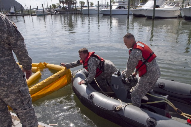 Soldiers of the 824th Transportation Company (Heavy Watercraft) quickly responded to an explosion of a 28-foot fishing boat that occurred at the civilian side of the North Carolina State Port in Morehead City on April 3. They assisted in first aid and damage control until civilian authorities arrived. Here a spillage response boom is secured to prevent further contamination of the water by fuel and other possible hazardous material. The explosion occurred just prior to a ribbon cutting ceremony that was to celebrate the rebuilding of their pier that had been destroyed during Hurricane Irene. Pictured here are Staff Sgt. Bryan Hanlon, left, and Warrant Officer Candidate Robert Wallace.