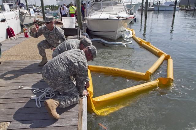Soldiers of the 824th Transportation Company (Heavy Watercraft) quickly responded to an explosion of a 28-foot fishing boat that occurred at the civilian side of the North Carolina State Port in Morehead City on April 3. They assisted in first aid and damage control until civilian authorities arrived. Here a spillage response boom is secured to prevent further contamination of the water by fuel and other possible hazardous material. Pictured are Chief Warrant Officer 3 Randy Grady, Spc. Paul Buelin and Staff Sgt. Scott Dowling.