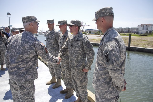 Maj. Gen. Peter Lennon, commanding general of the 377th Theater Sustainment Command, hands out challenge coins to the Soldiers of the 824th Transportation Company (Heavy Watercraft), who quickly responded to an explosion of a 28-foot fishing boat that occurred at the civilian side of the North Carolina State Port in Morehead City on April 3. Pictured here is Spc. Paul Buelin.