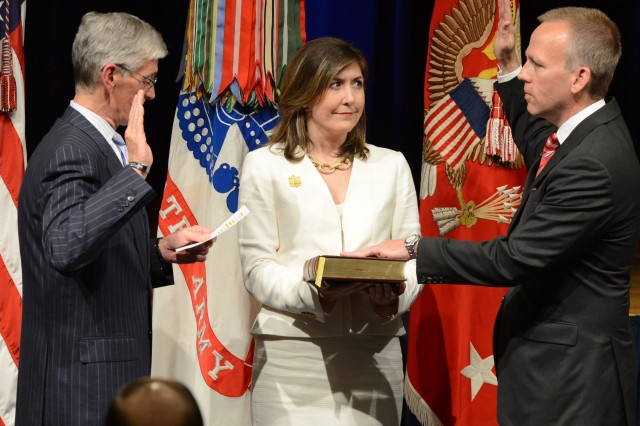 Secretary of the Army John McHugh (left) administers the oath of office to the new Under Secretary of the Army Brad R. Carson at the Pentagon, May 9, 2014. Julie, Carson's wife, is with him.
