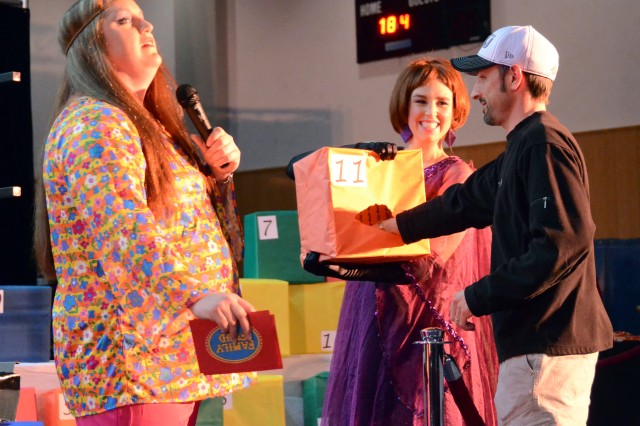 """Derek Hyde, right, school liaison officer, chooses a mystery prize May 3 at the second-annual Retro Game Show Night at Katterbach Fitness Center, hosted by the Ansbach Spouses' and Civilians' Club. Dana Mullins, left, hosted the first portion of Retro Game Show Night, including """"Family Feud."""""""