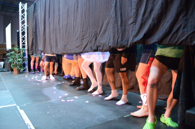 """Men line up during the """"Best Legs Contest"""" May 3 at the second-annual Retro Game Show Night at Katterbach Fitness Center, hosted by the Ansbach Spouses' and Civilians' Club."""