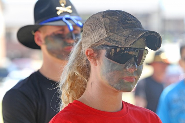 One of nearly 30 spouses from 3rd Squadron, 1st Cavalry Regiment, 3rd Armored Brigade Combat Team, 3rd Infantry Division, listens intently during a CBRN-E lane, April 26, at Sledgehammer Field. The women formed up and marched to various lanes throughout Kelley Hill, where they had to fire weapons at the Engagement Skills Trainer, don a pro-mask during a chemical attack, provide aid to a casualty while preparing him for a medical evacuation, react to contact while calling for fire, and answer cavalry-related questions during a Spur Board.