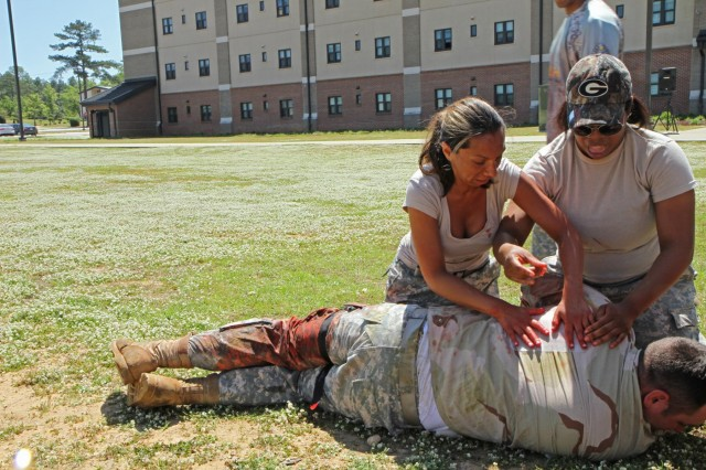 Two spouses from 3rd Squadron, 1st Cavalry Regiment, 3rd Armored Brigade Combat Team, 3rd Infantry Division, assess a casualty's exit wound, April 26, during the medical aid and evacuation lane. The spouses, who worked in six- and seven-person teams, went through six lanes as part of the squadron's Spouses' Spur Ride.