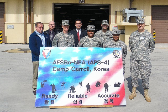 This group gathers outside APS  storage facilities Feb. 26. Front row, from left: Tom Bauer, ASC-Army Reserve Element; Lt. Col. Gary Cregan, commander, Army Field Support Battalion-Northeast Asia; Lt. Col. Hope Wright, Army Reserve Sustainment Command; Master Sgt. Theresa Lemus, ARSC; and Col. Milford Nichols, Operations, ARSC. Back row, from left: Stephen Brandt, supervisor chief, AFSBn-NEA; Joseph Springer, deputy commander, AFSBn-NEA; and Capt. Gannon Hendrick, executive officer, 416th AFSB. (Courtesy photo)