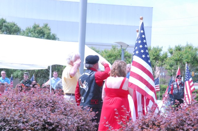 "USASOC honoree Hester ""Hoopy"" Qualls salutes as an American flag is placed in his honor. (Pictured l-r -- Hoopy Qualls, a member of the Rolling Thunder honor guard, and Hoopy's wife, Sissy Qualls.)"