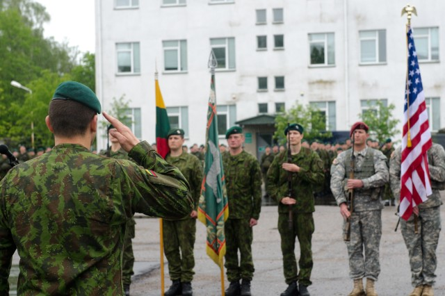 """Lithuanian army Maj. Gen. Almantas Leika, commander of the Lithuanian Land Forces, renders honors to Lithuanian and American flags during a ceremony to open Exercise Black Arrow 14 in Rukla, Lithuania, May 12, 2014. Black Arrow is a tactical field exercise that will train about 1,500 U.S. paratroopers from the 173rd Airborne Brigade """"Sky Soldiers,"""" and Lithuanian troops from the """"Iron Wolf"""" Mechanized Infantry Brigade, focusing on defensive operations and interoperability between the two forces and will include a combined airborne operation."""