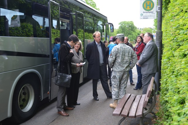 Col. Christopher M. Benson, foreground second from right, U.S. Army Garrison Ansbach commander, and Kevin Griess, right, deputy to the garrison commander, greet members of Ansbach's city council and representatives of the media. Benson and several representatives of garrison directorates and other organizations  took the host nation government officials and members of the media through Katterbach Kaserne and Urlas Housing by bus May 9, 2014. (U.S. Army photo by Bryan Gatchell, USAG Ansbach Public Affairs)