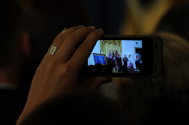 A woman in the audience captures the Medal of Honor ceremony of former Army Sgt. Kyle J. White, who received the nation's highest military award for his life-saving actions during an ambush in Afghanistan on Nov. 9, 2007. President Barack Obama presented the medal to White at the White House, May 13, 2014.