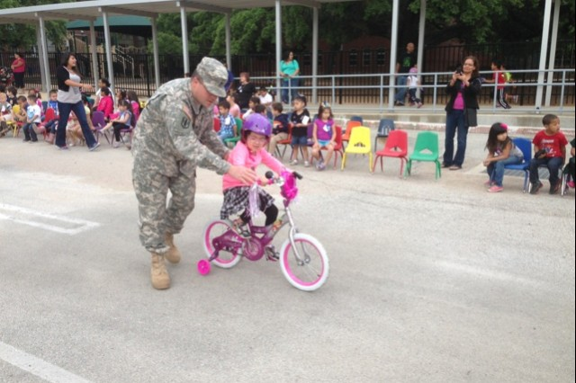 Staff Sgt. Brian Roussel assists a student during Lamar Elementary School's Bicycle Rodeo May 2, 2014, in San Antonio. Sergeant Roussel is a contract administrator with the 412th Contracting Support Brigade at Joint Base San Antonio-Fort Sam Houston. (U.S.Army photo)