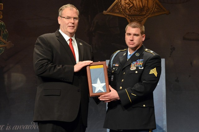 Former Army Sgt. Kyle J. White receives an encased Medal of Honor flag, as he is inducted into the Pentagon Hall of Heroes, May 14, 2014, one day after receiving the Medal of Honor for actions in Afghanistan during the Battle of Aranas, in 2007. Pictured with White is Deputy Secretary of Defense Robert O. Work.