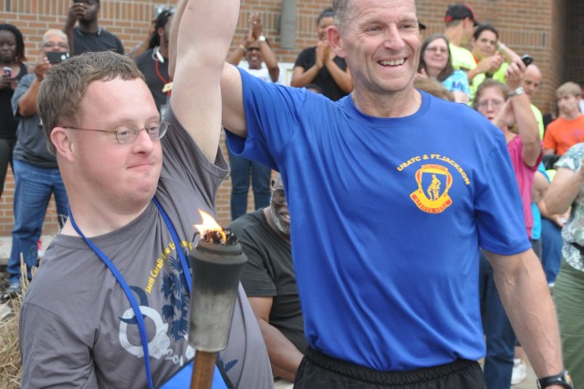 Brig. Gen. Bradley Becker, Fort Jackson's commanding general, and Special Olympics athlete Brad Hammond celebrate after Hammond lit the Special Olympics flame in front of Fort Jackson's Solomon Center May 9, 2014.
