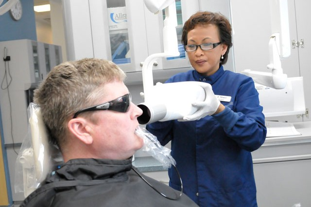 Dental assistant Johanna Miner takes an x-ray of Master Sgt. Dennis McFarland's teeth at the new Logan Dental Clinic. The new facility boasts an x-ray machine, previously not available at the old facility, which provides three-dimensional data using a cone-shaped beam.