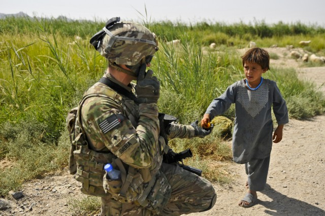 FORWARD OPERATING BASE ZANGABAD, Afghanistan -- U.S. Army Spc. Matthew Semeria with Troop B (Bull Troop), 1st Squadron, Combined Task Force Dragoon, gives candy to a local Afghan child during a foot patrol Aug. 13, 2013 at Forward Operating Base Zangabad, Afghanistan. Semeria and his platoon secured the base and spoke with members of the local community.