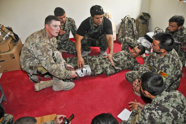 FORWARD OPERATING BASE LINDSEY, Afghanistan -- U.S. Army Sgt. Brian Mcintire (left) with 4th Squadron, Combined Task Force Dragoon, Security Force Assistance Team 401, teaches Afghan National Army soldiers with 2nd Mobile Strike Force Brigade, how to properly apply a tourniquet Aug. 24, 2013 at Camp Hero, Afghanistan. Mcintire extends his knowledge and experience to the ANA through a series of classes designed to teach them the fundamentals of medical aid.