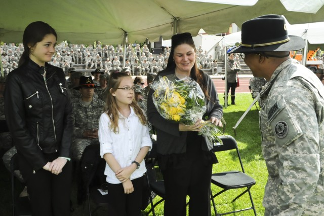 ROSE BARRACKS, Germany -- A Soldier with 2d Cavalry Regiment presents a bouquet of yellow roses to the family of an incoming command sergeant major during the change of responsibility ceremony held at Rose Barracks, Germany, May 15, 2014.
