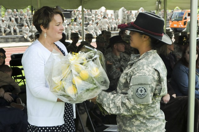 ROSE BARRACKS, Germany -- A Soldier assigned to 2d Cavalry Regiment presents a bouquet of yellow roses to a family of an incoming command sergeant major during the change of responsibility ceremony held at the Rose Barracks, Germany, May 15, 2014.