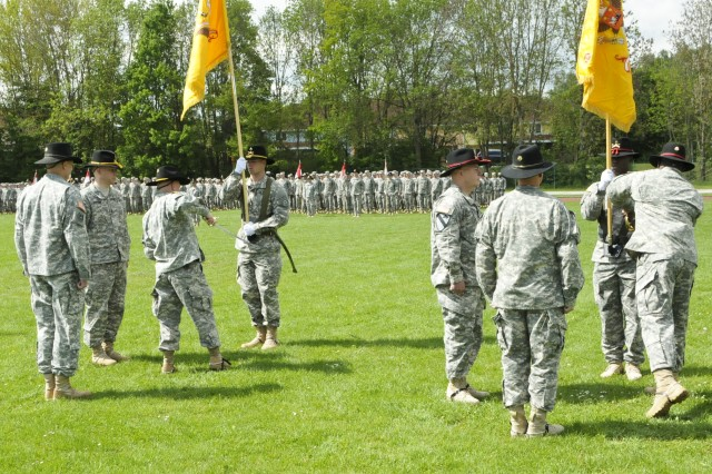 ROSE BARRACKS, Germany -- Command Sergeants Major Robert Ochsner (left middle), and Stanley Akins (far right), senior enlisted advisors of 4th Squadron and Fires Squadron, 2d Cavalry Regiment, respectively, draw the sabers from the guidon bearers sheath during the change of responsibility ceremony held at Rose Barracks, Germany, May 15, 2014.