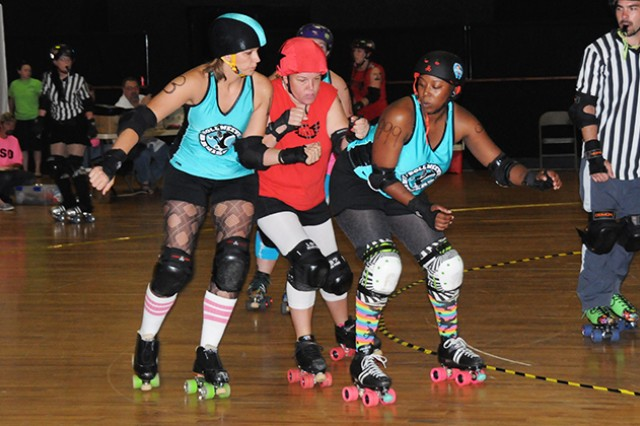 CW3 Jessica Brewington, A Company, 1st Battalion, 145th Aviation Regiment, and Aquila Lindsey, civilian, try to stop the opposing team's jammer from scoring points.
