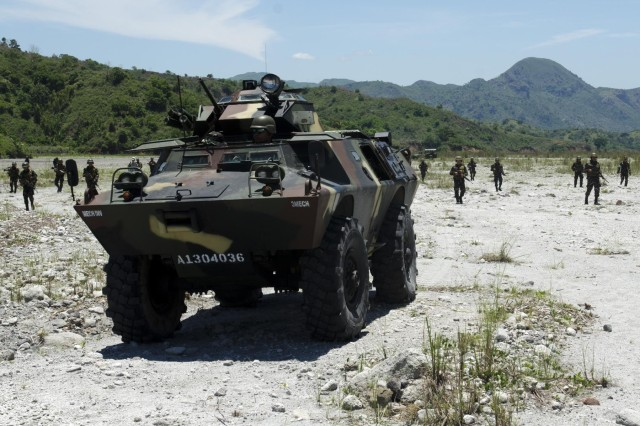 Infantrymen from the 20th Infantry Battalion, 8th Infantry Division, Philippine Army, follow behind a Simba armored personnel carrier during a multinational, joint force live-fire exercise rehearsal, May 13, as part of Balikatan 2014. Balikatan is an annual bilateral training exercise between the Philippines and U.S. designed to foster cooperation and interoperability between the two nations' armed forces through training as well as humanitarian aid and disaster relief projects. (U.S. Army photo by Staff Sgt. Chris McCullough)