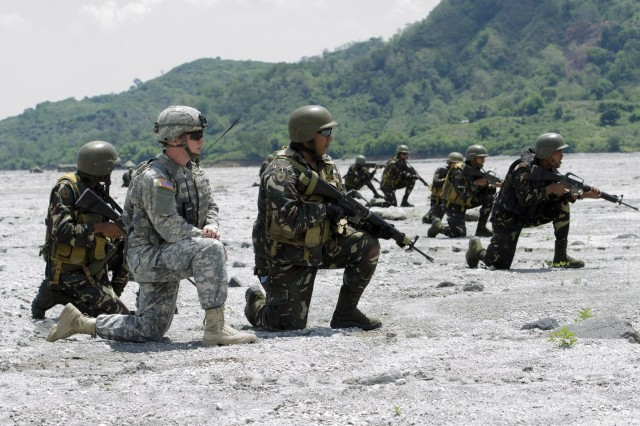 U.S. Army 1st Lt. Nathanial Frei, second from left, from 2nd Battalion, 3rd Infantry Regiment, 3-2 Stryker Brigade Combat Team, 7th Infantry Division, waits to advance along with Filipino soldiers from the 20th Infantry Battalion, 8th Infantry Division, during a multinational, joint force live-fire exercise, May 15, as part of Balikatan 2014. Balikatan is an annual bilateral training exercise between the Philippines and U.S. designed to foster cooperation and interoperability between the two nations' armed forces through training as well as humanitarian aid and disaster relief projects. (U.S. Army photo by Staff Sgt. Chris McCullough)