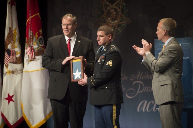 Former Army Sgt. Kyle J. White receives an encased Medal of Honor flag, as he is inducted into the Pentagon Hall of Heroes, May 14, 2014, one day after receiving the Medal of Honor for actions in Afghanistan during the Battle of Aranas, in 2007. Pictured with White is Deputy Secretary of Defense Robert O. Work and Under Secretary of the Army Brad R. Carson.  (U.S. Army photo by Staff Sgt. Bernardo Fuller)